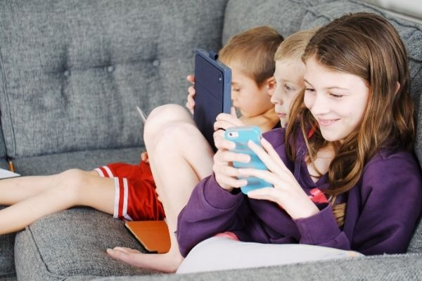 kids seating on couch and playing on mobile phone